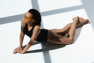 african american seductive girl sunbathing in black swimsuit and protective orange goggles  on floor with shadows