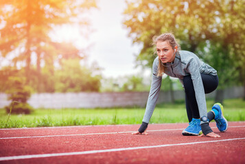 Athletic woman on running track getting ready to start