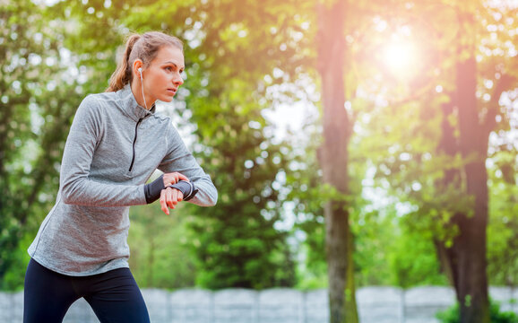 Athletic woman before start running setting up her smart watch