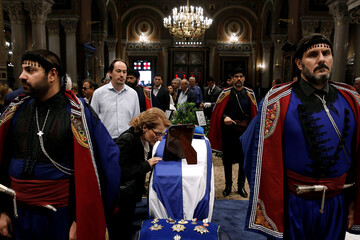 A woman pays her last respects to the flag-draped coffin of former Greek Prime Minister Constantine Mitsotakis inside the Athens Metropolitan Cathedral in Athens