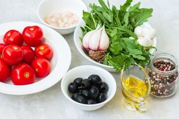Ingredients for healthy salad. Tomatoes, rucola, onion, mozzarella, olives, garlic and pepper with olive oil on a white stone background.