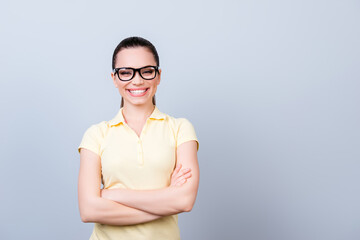Close up portrait of successful and confident lady standing with crossed hands on pure backgrund and looking in the camera, She is in a casual outfit, glasses, smiling