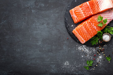 Raw salmon fish fillet on black background