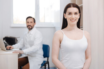 Enthusiastic graceful woman visiting plastic surgeon for lifting procedure