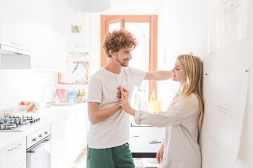 young couple indoor kitchen having conversation