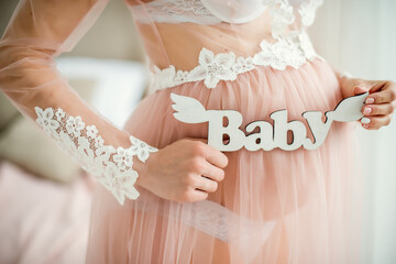 A pregnant woman is holding a wooden sign baby. Close up