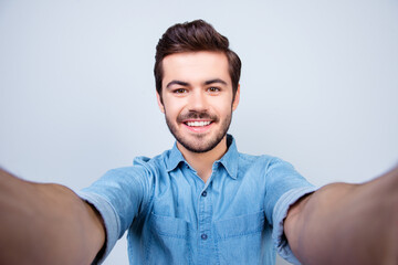 Handsome brunet young man is making selfie and smiling. He is wearing jeans shirt and behind him is a light blue background