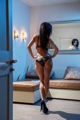 Beautiful girl sexy brunette in lingerie posing by the window, night