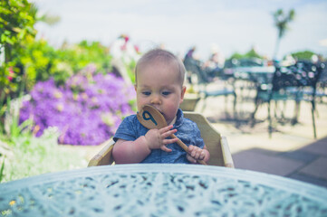 Baaby at table chewing on spoon