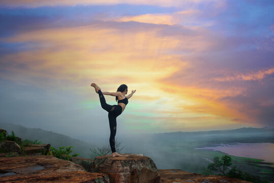 young woman practice yoga on high stage of rock with mountain and river in bottom background