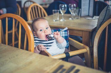 Baby in restaurant with spoon
