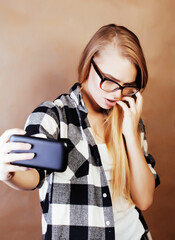 young pretty blond hipster girl making selfie on warm brown back