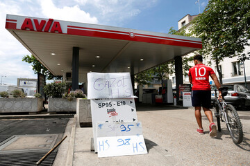 Signs indicate a petrol station is out of gasoline and diesel as a strike by transporters of hazardous materials continues to impact fuel distribution across the country, in Paris