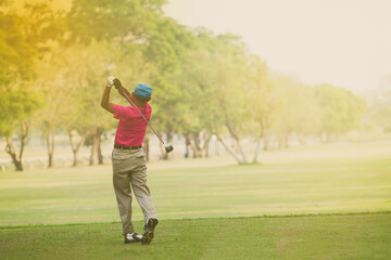 Asian golfers hit sweeping and keep golf course in the summer for relax time,soft focus and blurry