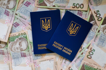 Two international passport of Ukrainians lie on pile of money from five hundred-pound banknotes. Passports for departure to Europe without visas. Visa-free regime for Ukraine.