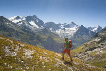 Hiker walking uphill with mountain range in background