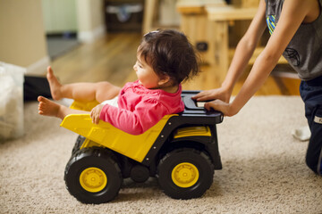 A Japanese American one year old baby girl is pushed in a toy dump truck by her older brother.