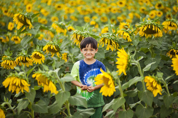 A four year old Japanese American boy stands in a tie-dy shirt it the middle of a field of sunflowers.