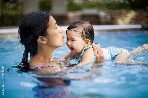 A Japanese American Mother Swims And Holds Her 10 Month Old Baby Girl In A Swimming Pool