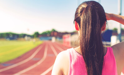 Female athlete looking out at a running track
