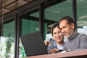 Smiling Attractive mature man with white stylish short beard using laptop with charming woman teenage. Serving internet via his gadget. Teaching old man using social network technology