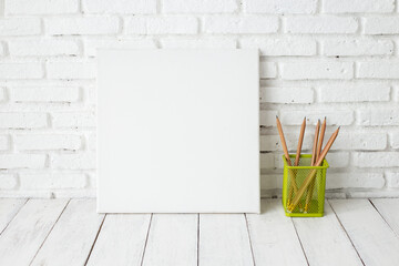 Empty white canvas frame on a wooden table