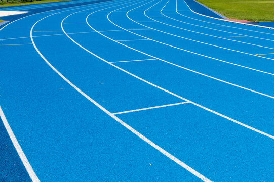 Blue Running track .Lanes of blue running track.Running track with blue asphalt and white markings in outdoor stadium.selective focus.