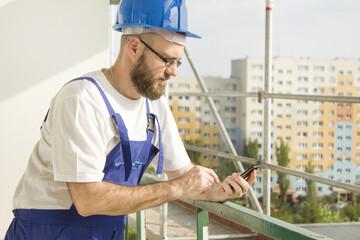 Fototapeta Pracownik budowlany w stroju roboczym i w kasku na głowie trzyma w ręku telefon komórkowy i wybiera numer. Praca na dużej wysokości. Rusztowania w tle. obraz
