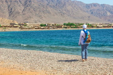 Young Lady Standing by the Cottage in a Camp in Sinai, Taba desert with the Background of the Sea and Mountains.
