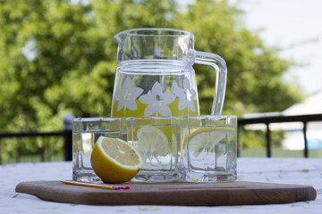 Glasses and jug with fresh lemonade on table