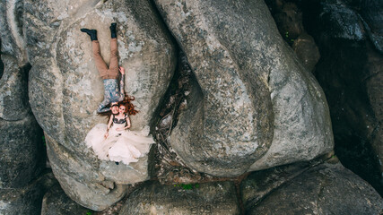Young couple lying on the edge of a cliff around nature and circle arch. Man with long hair beard and tatto. Woman in white and black dress and long red hair. Aerial.