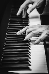 male musician hands playing on piano keys, black and white. music background