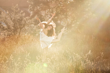 Beautiful Young Woman Dancing in the Sunlight in Nature