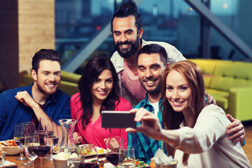 friends taking selfie by smartphone at restaurant