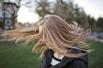 Happy teenage girl shaking head while standing in yard