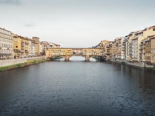 Ponte vecchio over Arno River in city against sky