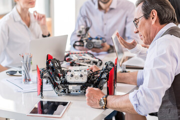 Group of inventors constructing devices in office