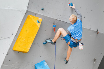 Male Climber sportsman hanging on artificial Climbing Wall, Competition in difficulty contest