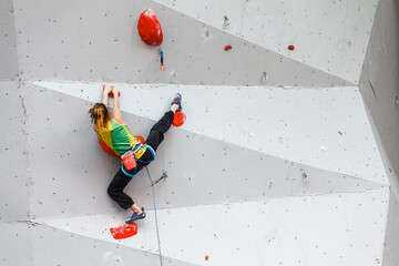 A woman athlete climbs the wall on an artificial climbing wall and in an attempt to take a difficult route do the splits
