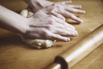 Woman kneading a dough on the table