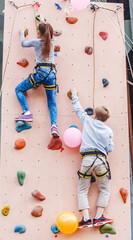 Free climber kid boy and girl practicing on artificial boulder rock wall in gym