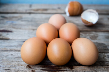 fresh eggs and egg shell on wooden background