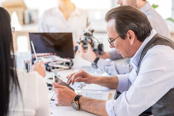 Concentrated mature man working with his team in office