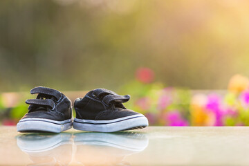 Toddler kid shoes on table in home garden.