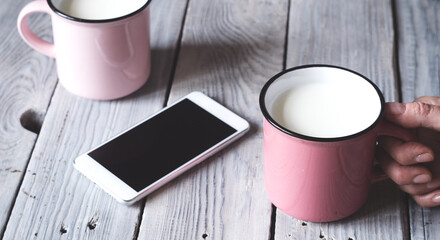 Two pink cups with milk on a white wooden table