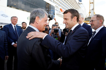 French President Macron greets Mediterranean Shipping Company (MSC) Chairman Gianluigi Aponte during a visit at the STX Les Chantiers de l'Atlantique shipyard site in Saint-Nazaire
