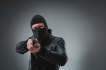 Robber with a gun, studio shot
