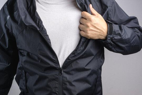 Man wearing black anti static or wet weather jacket or rain coat
