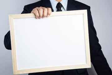 Business man hand holding blank wooden frame