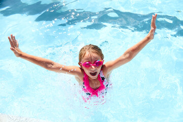 Happy little girl having fun in swimming pool